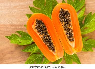 Papaya fruit on wooden background.Slices of sweet papaya on wooden background,Halved papayas with leaves,