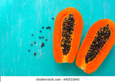 Papaya fruit on wooden background.Slices of sweet papaya on wooden background,Halved papayas with leaves,