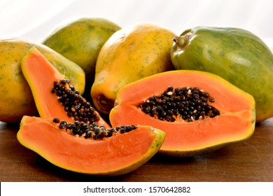 The papaya fruit, slices and seeds on a wooden table and a white background