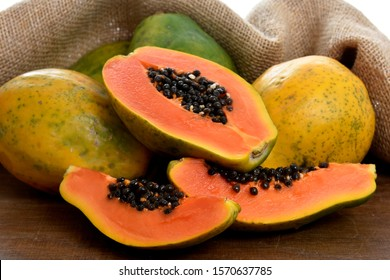 The papaya fruit  and slices whith seeds on a wooden table and a rustic fabric at the background