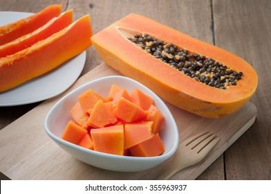 Papaya orange fresh on white dish  and papaya slice put on the wooden floor.