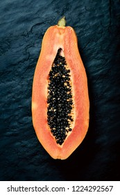 Papaya (Paw Paw) sliced in half and viewed from above on dark blue black slate rock