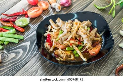 Papaya salad and chicken foot on black dish