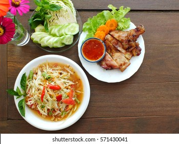 papaya salad and grilled chicken thai food on  table