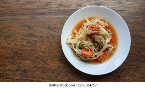 """Papaya salad on wood table. The popular thai food is called """"Som Tum Thai"""""""