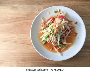 Papaya salad on the wooden texture table.Thai cuisine spicy SOMTAM