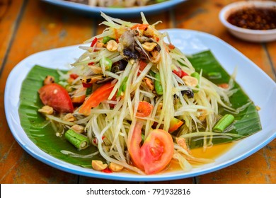 Papaya salad in a plate on a table.
