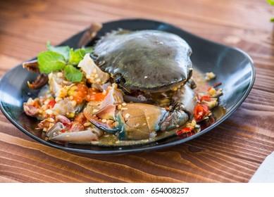 Papaya salad with raw sea crab  on black dish