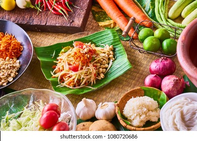 Papaya salad (Som Tam)  in banana leaf dish on traditional mat  decorating with many ingredients such garlic, shallot, papaya, tomato, cow pea, Fermented Rice Flour Noodles, palm sugar, sticky rice