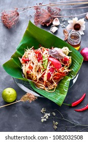 Papaya salad (Som Tam) with crab or Som tam Poo in banana leaf dish  on the stone table prepare for serviing,  decorated with shallot, chilli, dry flowers&leafs, and honey glass