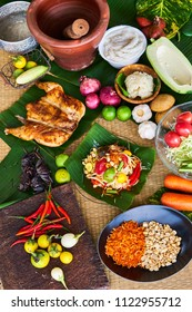 Papaya salad (Som Tam) , Thai food,  in banana leaf dish on traditional mat  decorating with  ingredients such garlic, shallot, papaya, tomato, cow pea, Fermented Rice Flour Noodles, sticky rice, lime