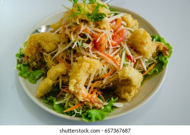"Papaya salad Thai stye ""SomTam""  on top with fired shrimp on white dish.Diet food for healthy."