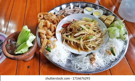 Papaya salad in a tray that has side dishes