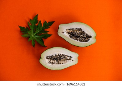 Papaya sliced in half and its green leaf styled against a vibrant orange background with copy space. Healthy natural food, flat lay photo