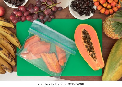 Papaya slices  in a plastic bag with fruits and knives on a green cutting board.