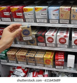 PAPENBURG, GERMANY - AUGUST 11, 2015: Boxes of cigarettes in a Marktkauf Hypermarket. Warning signs on cigarette packs, warning of smoking dangers, increased quit attempts among smokers.
