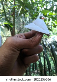 Paper airplane in Asian left hand with nature blur background