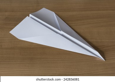 Paper Airplane in claccic arrow shape on a wooden table