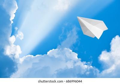 Paper airplane flying in the sky among the clouds
