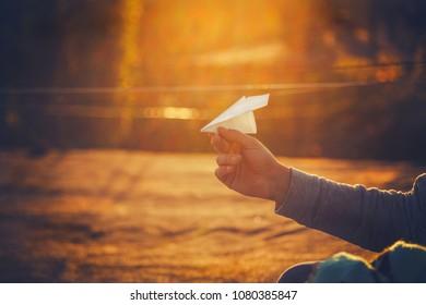 Paper airplane in man's hand at orange sunset.