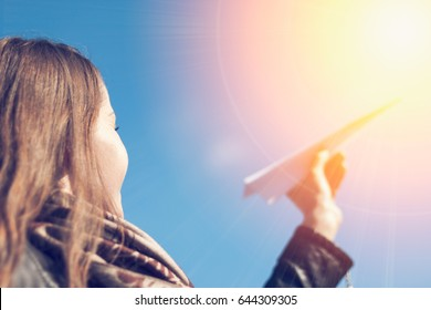 Paper airplane in woman hand and sunlight