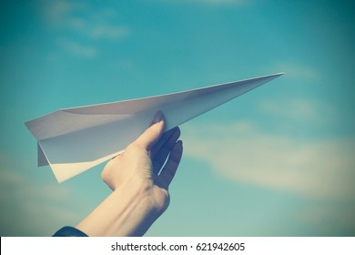 Paper airplane in woman hand toned