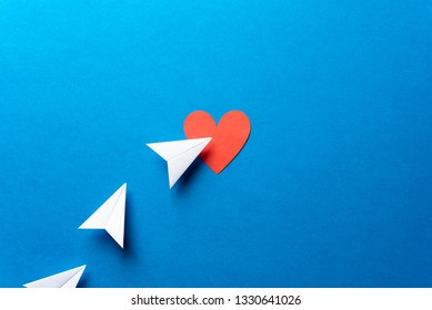 Paper airplanes with red heart shape on blue background. Sharing and send concept. Sharing and send symbol concept. Airplane flight transport sign. Landing page concept. Paper plane email web message