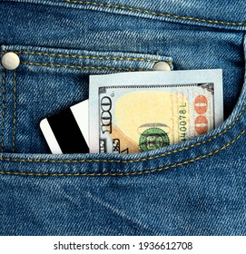 paper american dollars and plastic bank card with magnetic stripe in the pocket of blue jeans, close up