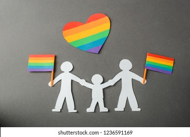 Paper art of gay couple and  child with rainbow flags and heart. Love wins, equal rights for LGBT people.