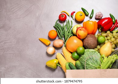 Paper bag with assortment of fresh organic fruits and vegetables on grey table, flat lay. Space for text
