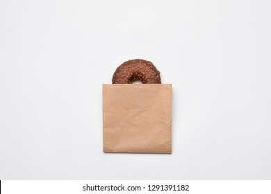 Paper bag with chocolate doughnut on white background, top view. Space for design