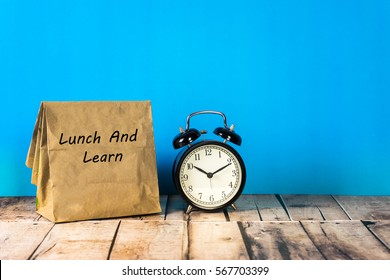 Paper bag and clock on blue background with a notes lunch and learn.