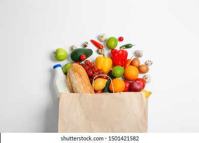Paper bag with different groceries on white background, top view
