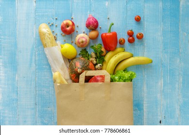Paper bag of different health food on blue wooden background. Top view. Flat lay