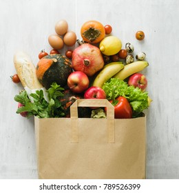 Paper bag of different health food on white wooden background. Top view. Flat lay