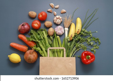 Paper bag of different tropical fresh fruits and vegetables. Healthy eating and grocery shopping concept. Top view. Flat lay