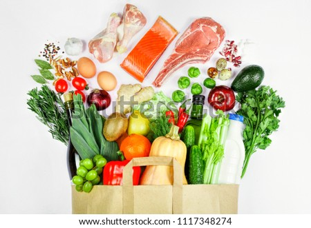 paper bag filled with different  quality food and a healthy meal on a white background. Full paper bag of health food. Top view. Flat lay
