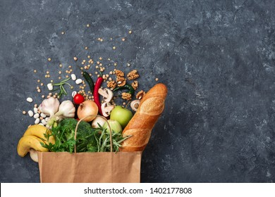 Paper bag food with vegetables and fruit on a dark background with copy space top view