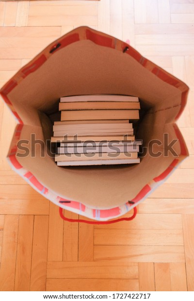 Paper bag fool of books on a wooden floor