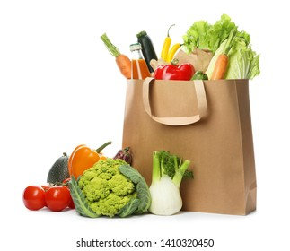 Paper bag with fresh vegetables and bottle of juice on white background