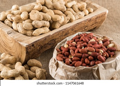 Paper bag full of peeled peanuts and peanuts in nutshell on a piece of wood