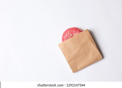 Paper bag with glazed doughnut on white background, top view. Space for text