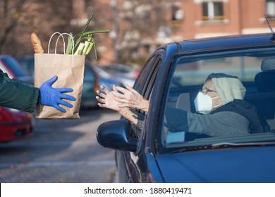 Papiersack mit Lebensmitteln, die an bedürftige ältere Menschen im Fahrzeug abgegeben werden