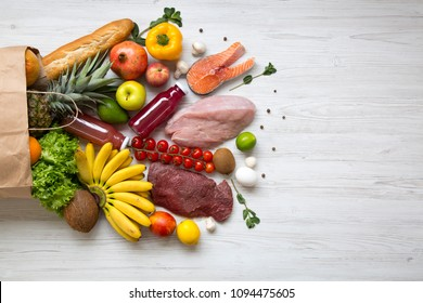 Paper bag of healthy raw food on white wooden table. Cooking food background. Flat-lay of fresh fruits, veggies, greens, different meat, top view, copy space. Shopping concept.