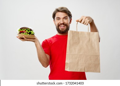 Paper bag man in a red shirt and a hamburger in his hand
