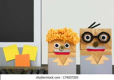 Paper Bag People Representing Tech Support Standing Beside A Computer