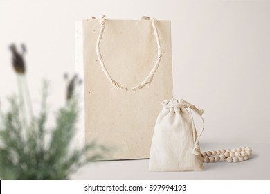 Paper bag and pouch mockup, front view, with decor elements, plants and blank copy, logo space on pastel background.