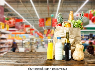 Paper bag with various food is on the table in the background of a supermarket