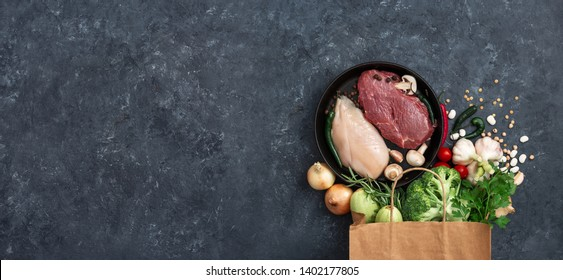 Paper bag vegetables, fruit and meat on dark background with copy space top view. Bag food concept