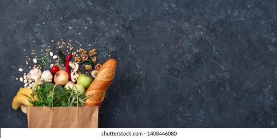 Papiersack Gemüse und Obst auf dunklem Hintergrund mit Kopienraum-Draufsicht. Bag-Food-Konzept